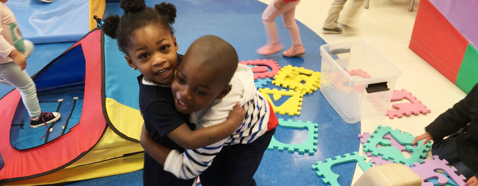 boy and girl hugging in preschool