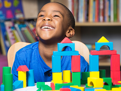 Curtis laughing playing with blocks at marcus autism center